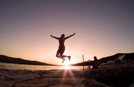 Girl jumping at sunset on the beach photo