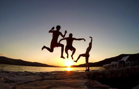 Silhouet van vrienden springen bij zonsondergang op het strand