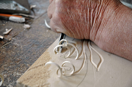 engraver: Hands of the craftsman carve a bas-relief in wood