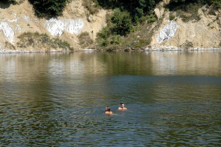 mud pit: OCNA SIBIULUI, ROMANIA - JULY 9: Unidentified people swimming and floating on the water of the abandoned salt mine. On July 9, 2005 in Ocna Sibiului (Vizakna, Salzburg), Romania