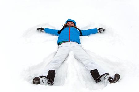 Beautiful girl making a winter snow angel photo
