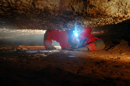 Narrow cave passage with a spelunker Stock Photo