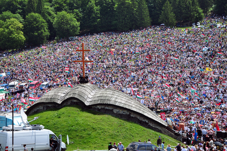 hundreds and thousands: CSIKSOMLYO, ROMANIA - JUNE 7: Crowds of Hungarian pilgrims gather to celebrate the Pentecost and the catholic pilgrimage on June 7, 2014 in Sumuleu Ciuc (Csiksomlyo), Romania