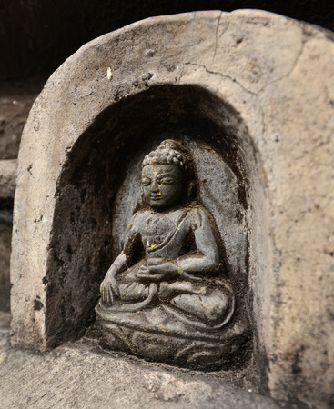 ancient yoga: SWAYAMBHUNATH  SEPTEMBER 29: Bas relief statuette of sitting Buddha now damaged after the massive earthquake that hit Nepal on April 25 2015. On September 29 2013 in Swayambhunath Nepal