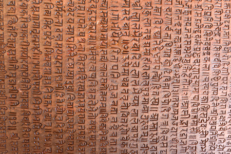 sanskrit: PASHUPATINATH  OCTOBER 10: Ancient sanskrit text on a stone background now damaged after the earthquake that hit Nepal on April 25 2015. On October 10 2013 in Pashupatinath Nepal