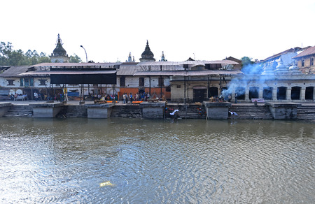 cremated: PASHUPATINATH  OCTOBER : Cremation ghats and ceremony along the holy Bagmati River. Hundreds of earthquake victims were cremated here after the catastrophe. On October 8 2013 in Pashupatinath Nepal