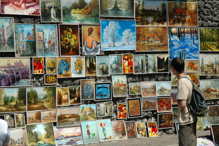 admires: KRAKOW, POLAND - MAY 29: Unidentified tourist admires the exhibited paintings for sale in the historical center of Krakow. On May 29, 2005 in Krakow, Poland