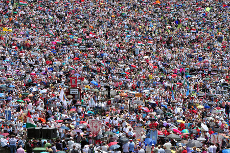 hundreds and thousands: CSIKSOMLYO ROMANIA  JUNE 7: Crowds of Hungarian pilgrims praying during the Pentecost and the catholic pilgrimage on June 7 2014 in Sumuleu Ciuc Csiksomlyo Romania