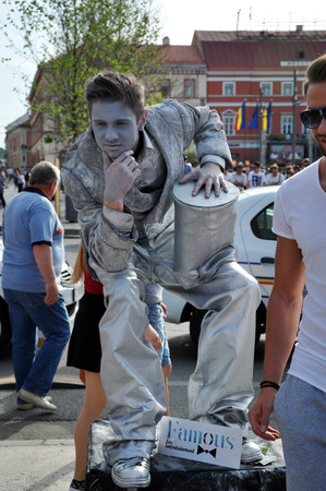 cluj: CLUJ NAPOCA  MAY 24: Living statue performer in a silver costume doing a busking mime inside the Man.In.Fest during the Cluj Days of Cluj. On May 24 2015 in in Cluj Romania Editorial