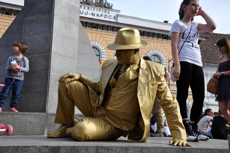 CLUJ NAPOCA  MAY 24: Living statue performer in golden costume doing a busking mime inside the Man.In.Fest during the Cluj Days of Cluj. On May 24 2015 in in Cluj Romania