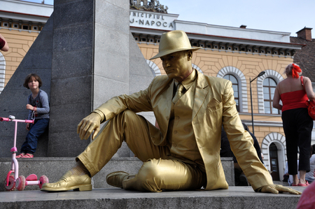 maffia: CLUJ NAPOCA  MAY 24: Living statue performer in golden costume doing a busking mime inside the Man.In.Fest during the Cluj Days of Cluj. On May 24 2015 in in Cluj Romania