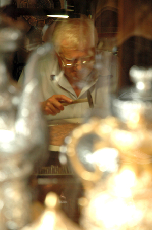 brazier: MOSTAR, BOSNIA AND HERZEGOVINA - AUGUST 7: Unidentified craftsman tinkering a copper dish in his small shop in the bazaar. On August 7, 2009 in Mostar, Bosnia and Herzegovina Editorial