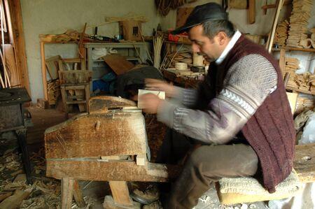 craftman: PATRAHAITESTI  CCA JUNE: Carpenter handcrafting a traditional Romanian wooden alpenhorn.The instrument was used in communication decades ago in the mountains. Cca June 2008 in Patrahaitesti Romania Editorial