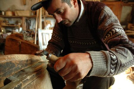 decades: PATRAHAITESTI  CCA JUNE: Carpenter handcrafting a traditional Romanian wooden alpenhorn.The instrument was used in communication decades ago in the mountains. Cca June 2008 in Patrahaitesti Romania Editorial