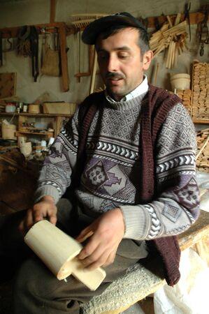 alphorn: PATRAHAITESTI  CCA JUNE: Carpenter handcrafting a traditional Romanian wooden alpenhorn.The instrument was used in communication decades ago in the mountains. Cca June 2008 in Patrahaitesti Romania Editorial