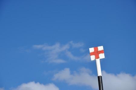 croix rouge: Trekking panneau dans les montagnes. Croix rouge sur fond blanc contre le ciel bleu Banque d'images