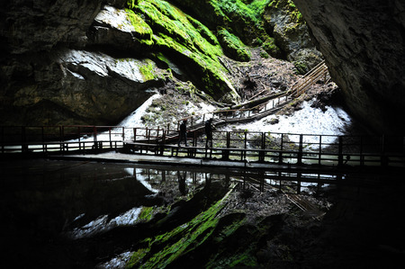 subterranean: SCARISOARA, ROMANIA - AUGUST 12, 2015: Unidentified tourists visiting the Scarisoara ice cave, the largest ice cave from Europe