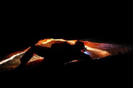 cave exploring: Spelunker exploring a narrow cave gallery