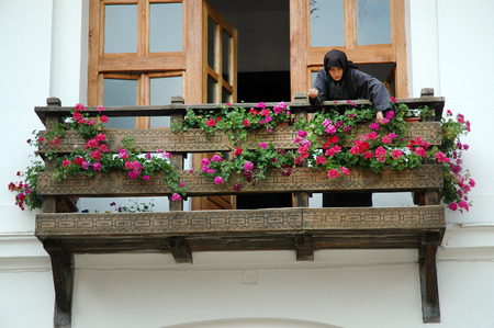 black nun: TISMANA, ROMANIA - AUGUST 21, 2008: A nun dressed in black waters the flowers on the balcony of the Monastery of Tismana, Romania