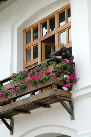 black nun: TISMANA, ROMANIA - AUGUST 21, 2008: A nun dressed in black waters the flowers on the balcony of the Orthodox Monastery of Tismana, Romania Editorial