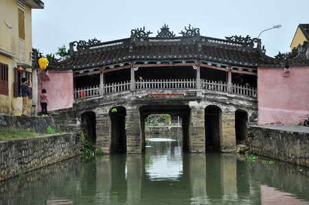 ponte giapponese: HOI AN, VIETNAM - MARCH 3, 2013: Tourists visiting the famous Japanese Bridge in the city of Hoi An, an important Southeast Asian trading port in the past
