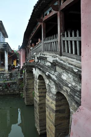 ponte giapponese: Hoi An, Vietnam - 3 MARZO 2013: turisti che visitano il famoso Ponte giapponese nella città di Hoi An, un importante porto commerciale sud-est asiatico nel passato Editoriali