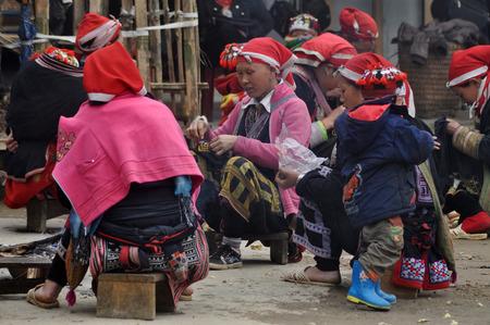 minority: SAPA, VIETNAM - FEBRUARY 24, 2013: Unidentified Red Dao Red Yao, Dzao women sewing in the village of Ta Phin. They are Chinese minority in Vietnam