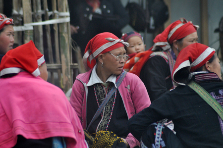 minority: SAPA, VIETNAM - FEBRUARY 24, 2013: Unidentified Red Dao Red Yao, Dzao women resting in the village of Ta Phin. They are Chinese minority in Vietnam Editorial
