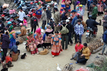traditional goods: SAPA, VIETNAM - FEBRUARY 22, 2013: Hmong women at Bac Ha market in Northern Vietnam. Bac Ha is hilltribe market where people come to trade for goods in traditional costumes