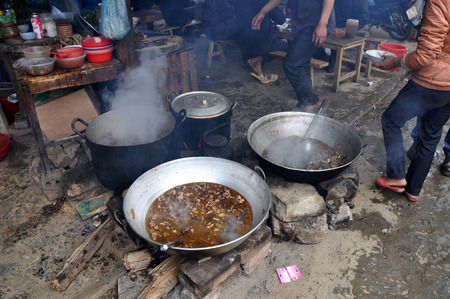 caldron: SAPA, VIETNAM - FEBRUARY 22, 2013: Meat boiling in a caldron at the rural market of Bac Ha, Northern Vietnam