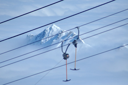 foreground focus: Ski lift in the Alps. Blurred foreground, focus on the mountains
