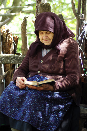 intercede: RAMETI, ROMANIA - JUNE 6, 2010: Elder woman reading the Bible. The older generations in the rural areas of Romania are very religious