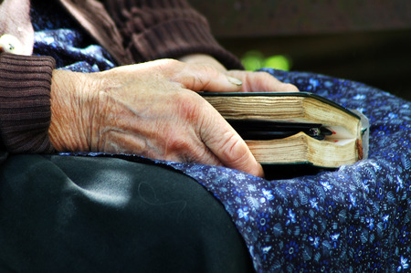 intercede: RAMETI, ROMANIA - JUNE 6, 2010: Elder woman holding a Bible in her hand. The older generations in the rural areas of Romania are very religious