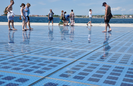 multilayer: ZADAR, CROATIA - AUG 25, 2014: People walking on Greeting to the Sun sculpture. It consists of 300 multilayer glass panels and uses solar power to create a light show at night