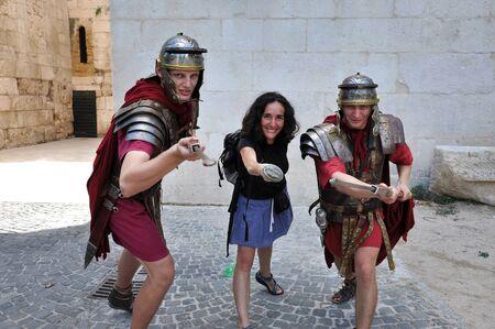 soldati romani: Spalato, Croazia - 26 agosto 2014: uomini vestiti da soldati romani in posa con una donna turistica nel centro storico di Spalato, Croazia