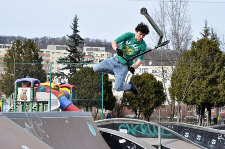 CLUJ-NAPOCA, ROMANIA - FEBRUARY 28, 2016: Young guy doing jumping tricks with his scooter in the Skate Park of Cluj Editorial