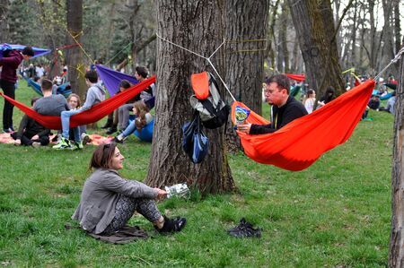 people relax: CLUJ-NAPOCA, ROMANIA - APRIL 1, 2016: Young people relaxing in hammocks in the Central park during the Big Hammock Day