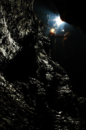 descends: Caver descends in a cave on a rope Stock Photo