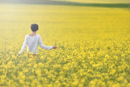 Happy woman walking through a canola field in the summer 免版税图像