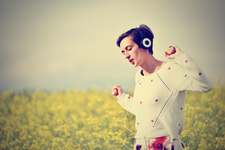 sexy headphones: Sexy young woman with headphones dancing in the outdoors Stock Photo