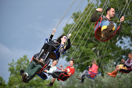 chairoplane: BONTIDA, ROMANIA - JULY 17, 2016: Young people enjoying swing ride, carousel, merry-go-round, highland spinner at Electric Castle Festival