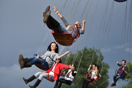 BONTIDA, ROMANIA - JULY 17, 2016: Young people enjoying swing ride, carousel, merry-go-round, highland spinner at Electric Castle Festival