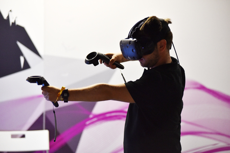 htc: CLUJ-NAPOCA, ROMANIA - AUGUST 5, 2016: Boy tries virtual reality HTC Vive headset and hand controls during the virtual reality exposition, at the Untold Festival
