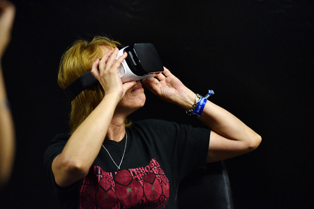 CLUJ-NAPOCA, ROMANIA - AUGUST 6, 2016: Woman tries virtual reality Samsung Gear VR headset and hand controls during the virtual reality exposition, at the Untold Festival Editorial