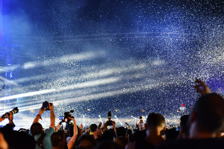 festival moments: CLUJ-NAPOCA, ROMANIA - AUGUST 7, 2016: Cannons throwing confetti and streamers over partying crowd at a Dj Armin van Buuren live concert at Untold festival