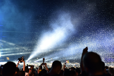 CLUJ-NAPOCA, ROMANIA - AUGUST 7, 2016: Cannons throwing confetti and streamers over partying crowd at a Dj Armin van Buuren live concert at Untold festival