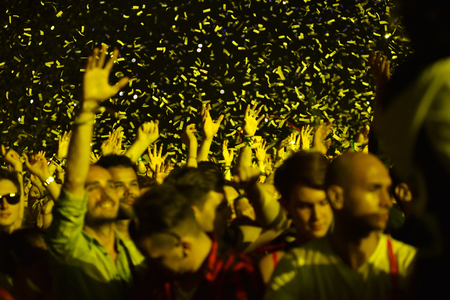 CLUJ-NAPOCA, ROMANIA - AUGUST 8, 2016: Crowd of people partying with raised arms and hands at a Afrojack concert during the Untold Festival