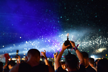 festival moment: CLUJ-NAPOCA, ROMANIA - AUGUST 7, 2016: Cannons throwing confetti and streamers over partying crowd at a Dj Armin van Buuren live concert at Untold festival
