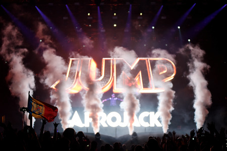 clubbers: CLUJ-NAPOCA, ROMANIA - AUGUST 8, 2016: Dj Afrojack mixing live on the stage during the Untold Festival. Beautiful stage lights in the background Editorial