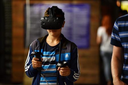 Cluj-Napoca, ROMANIA - 5 Agosto 2016: Il ragazzo cerca Comandi e mano HTC Vive realtà virtuale durante la realtà esposizione virtuale, al Festival di Untold
